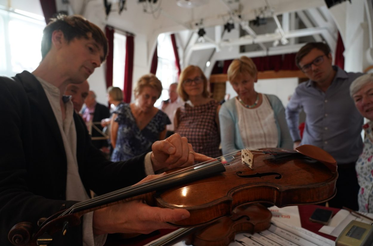 Matthew Truscott shows his violin to OAE supporters