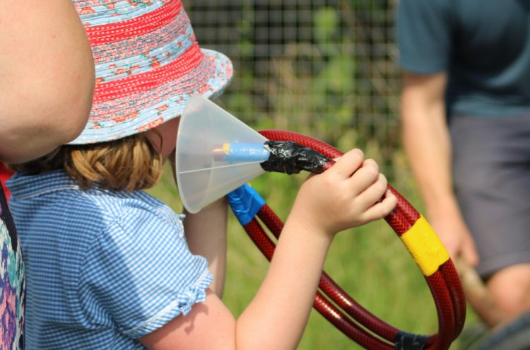 A young participant in Suffolk plays a hosepipe horn