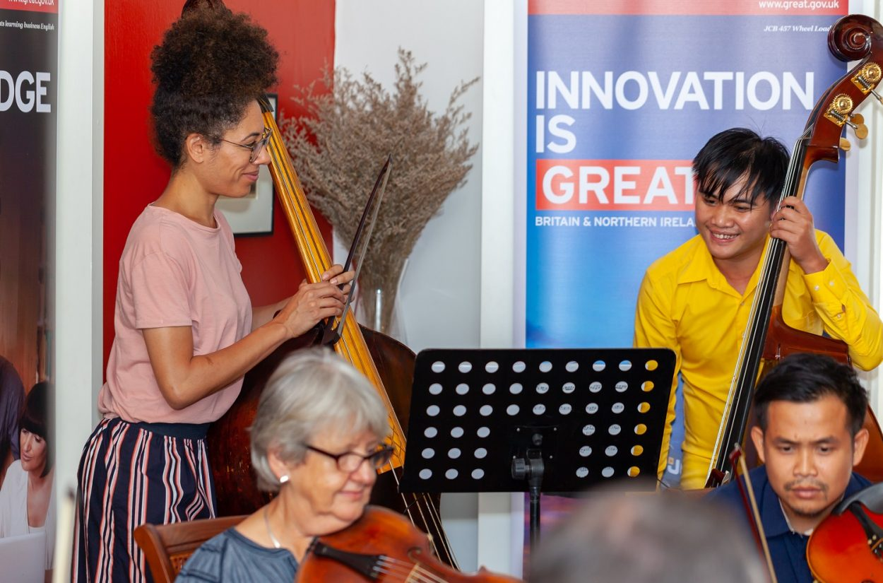Double bass Carina Cosgrave teaches a young music at a British Council event in Laos