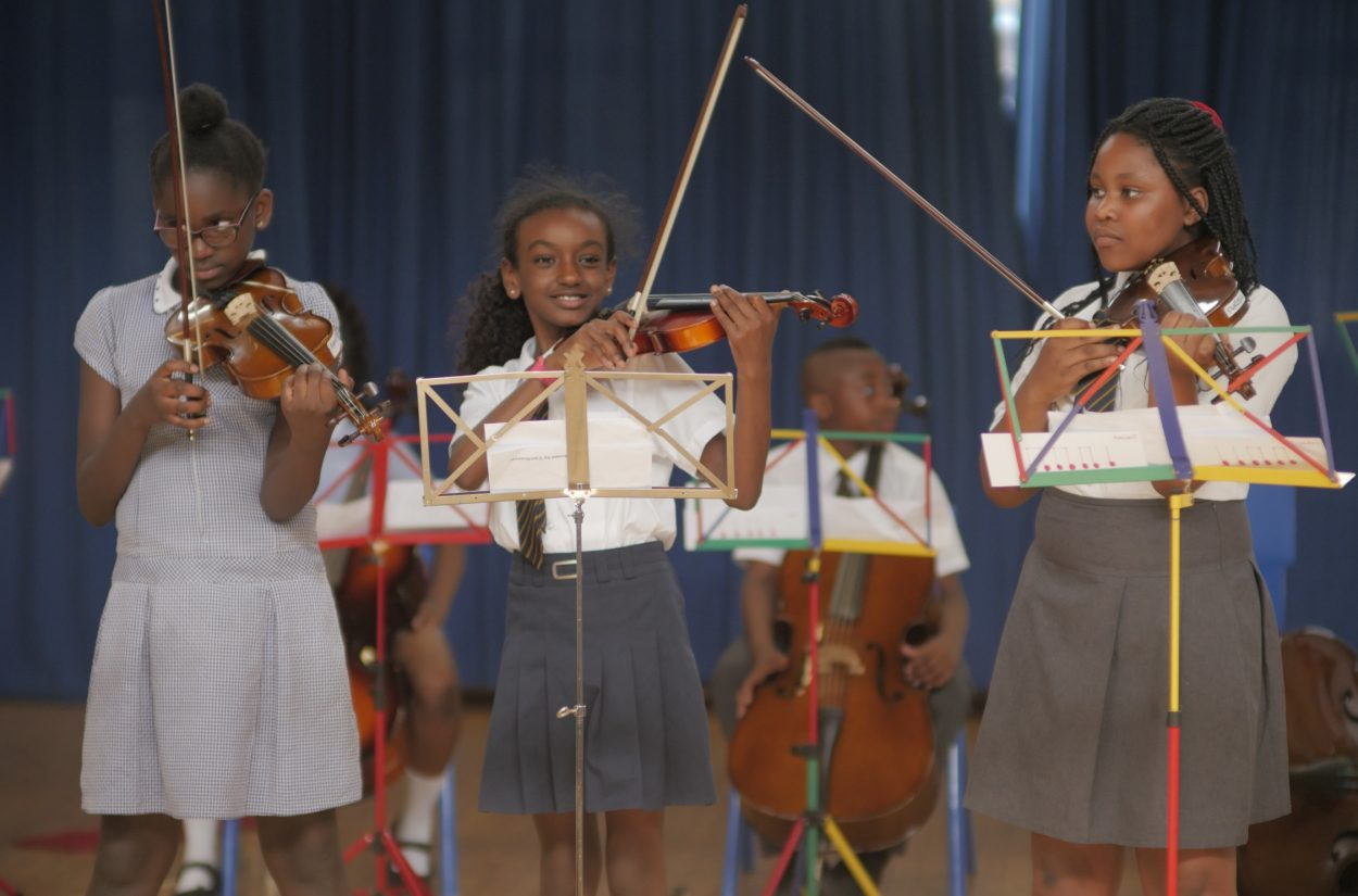 Three young musicians perform as part of the OAE's String Club